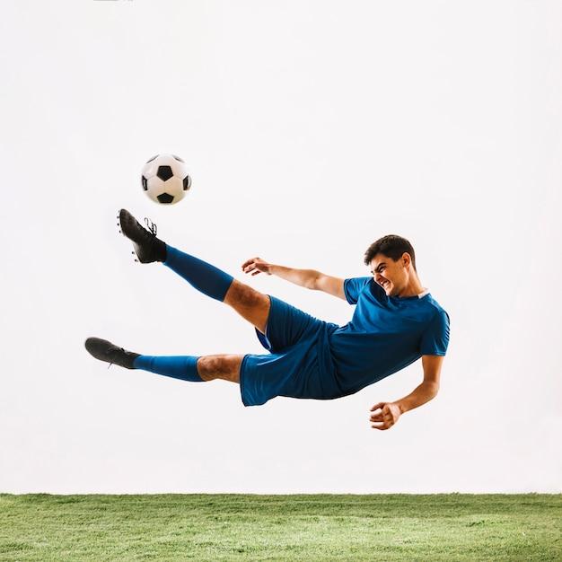 Athlete falling and kicking ball Free Photo