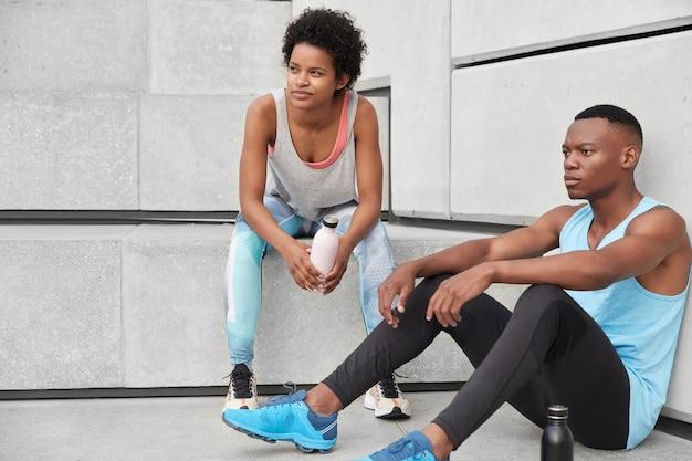 L'atleta e il corridore maschile si siedono sulle scale, immersi nei pensieri, vestiti con abiti casual, bevono caffè con indumenti sportivi, si sentono stanchi di riposo dopo aver fatto jogging. persone, motivazione, concetto di fitness Foto Gratuite