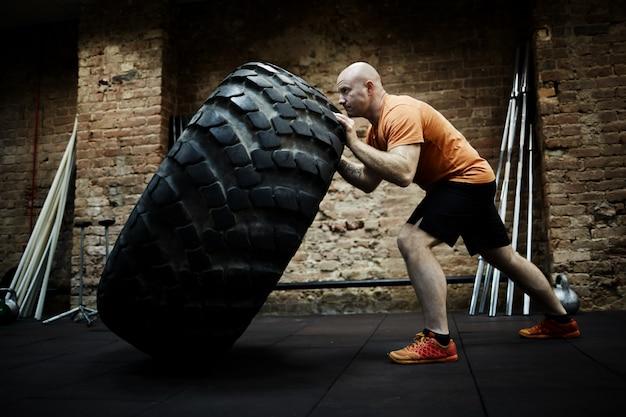 Athlete focused on tire flipping Free Photo