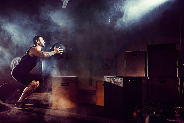 Athlete gave exercise. jumping on the box. phase touchdown. gym shots in the dark tone. smoke in gym. Premium Photo