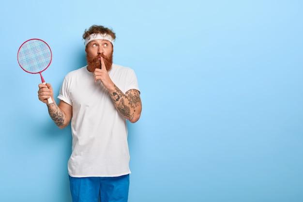 Спортсмен-хипстер с теннисной ракеткой в руке, жестикулирует, носит спортивную одежду, рассказывает секрет Бесплатные Фотографии
