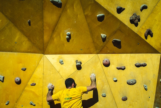 Athlete man trying to reach the top of a climbing wall with the strength of his hands and legs. Premium Photo