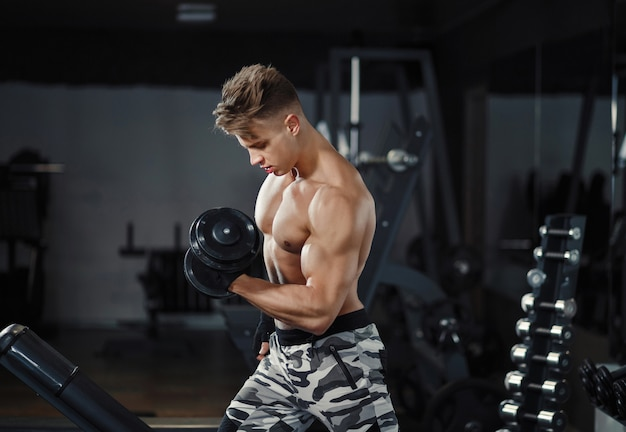 Athlete muscular bodybuilder training biceps curl with dumbbell in the gym Premium Photo