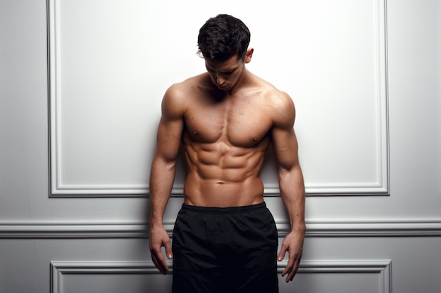 Athlete, muscular man at the white wall poses shirtless, showing six pack abs, white background. Premium Photo