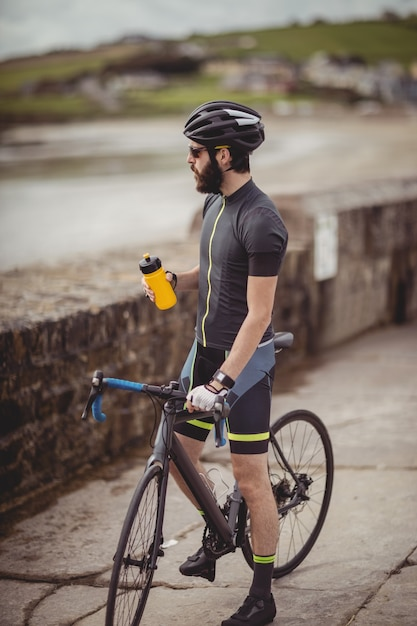 Athlete refreshing from bottle while riding a bicycle Free Photo