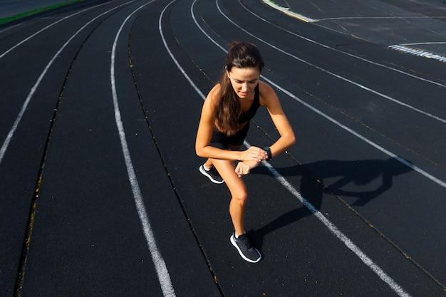 Бегун спортсмена работает на спортивной трассе тренировки ее кардио. женщина бег для соревнований на летнем открытом стадионе. Premium Фотографии