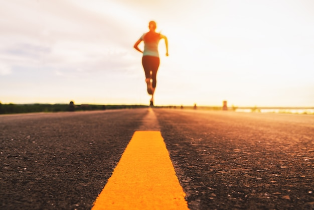 Athlete running on the road trail in sunset training for marathon and fitness. motion blur of woman exercising outdoors Premium Photo
