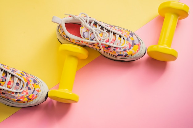 Athlete's set with female running sneakers and dumbbells yellow-pink background. fitness concept.  equipment for gym and home Premium Photo