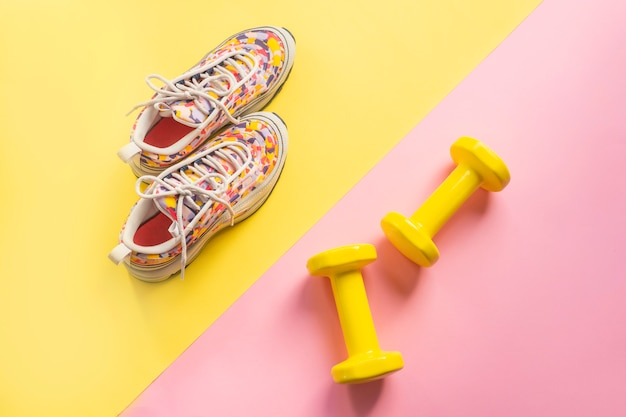 Athlete's set with female running sneakers and dumbbells yellow-pink background. Premium Photo