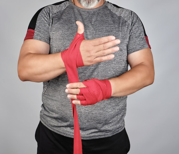 Athlete stand in gray clothes and wrap his hands in red textile elastic bandage Premium Photo