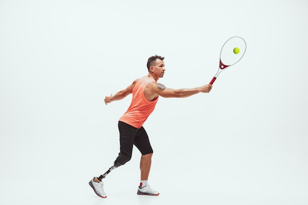 Athlete with disabilities or amputee isolated on white. professional male tennis player with leg prosthesis training Free Photo