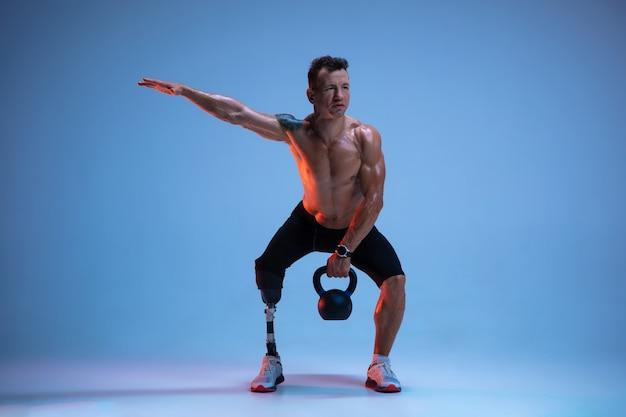 Спортсмен с ограниченными возможностями или инвалидом, изолированные на синем фоне студии. профессиональный спортсмен-мужчина с тренировкой протезирования ноги с гирями в неоне. Бесплатные Фотографии