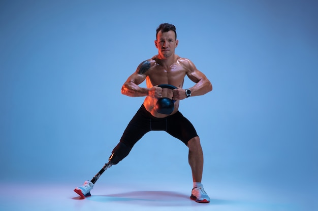 障害者または切断患者の青のスタジオの背景に分離された運動選手。ネオンの重みで脚義足トレーニングとプロの男性スポーツマン。 無料写真