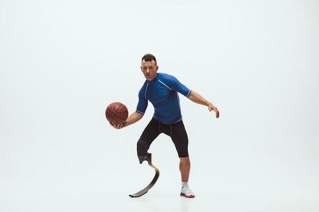 흰색 스튜디오 공간에 고립 된 장애 또는 수족 선수. 다리 보 철물 훈련 및 스튜디오에서 연습 전문 남성 농구 선수. 무료 사진