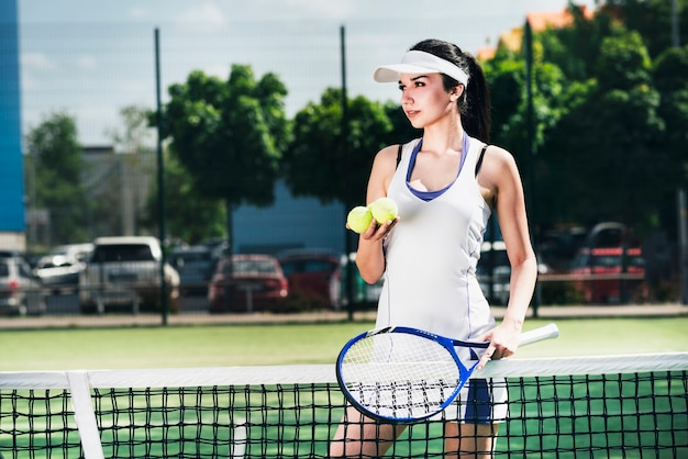 Athlete woman in sportswear holding racket and balls Free Photo
