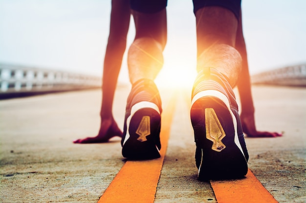 Спортсмены начинают с дороги с утренним солнцем. Premium Фотографии