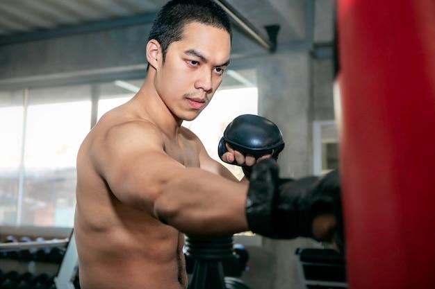 Athletes asian man boxer training on a punching bag at fitness gym. Premium Photo