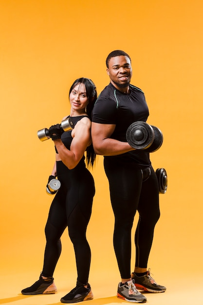 Athletes posing with weights Free Photo