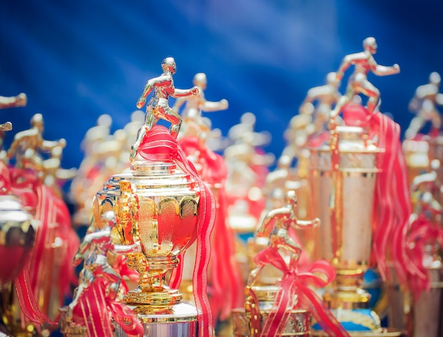 Athletes trophy cup awards with a red ribbon Premium Photo