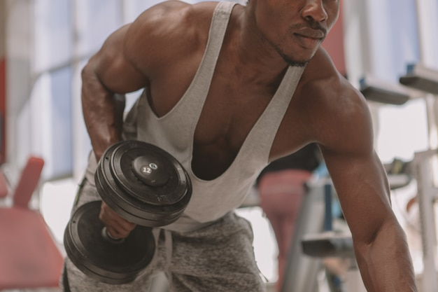 Athletic african man working out with dumbbells at the gym Premium Photo