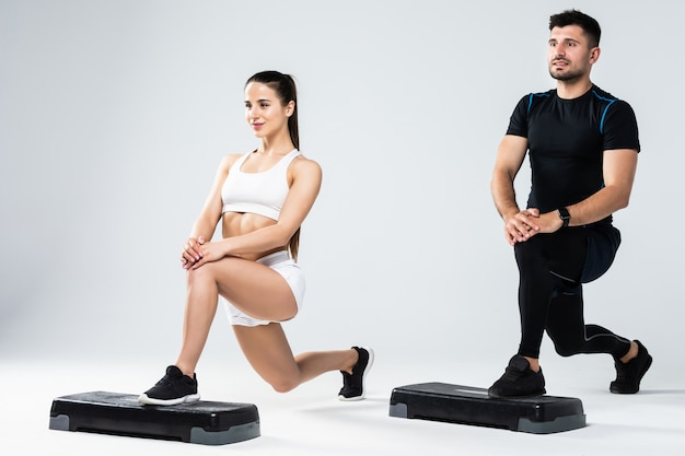 白い背景で隔離の好気性のクラスでのステップの上の演習を行う運動のカップル Premium写真