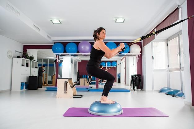 Athletic fit woman makes trx exercise Premium Photo