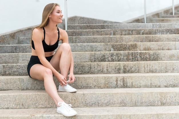 階段の上に立って、靴ひもを結ぶ運動少女 無料写真