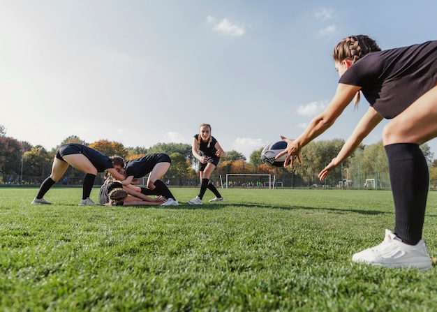 Athletic girl trying to catch a rugby ball Free Photo