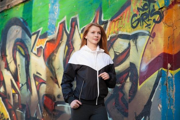 Athletic girl walking by bright graffiti wall Free Photo