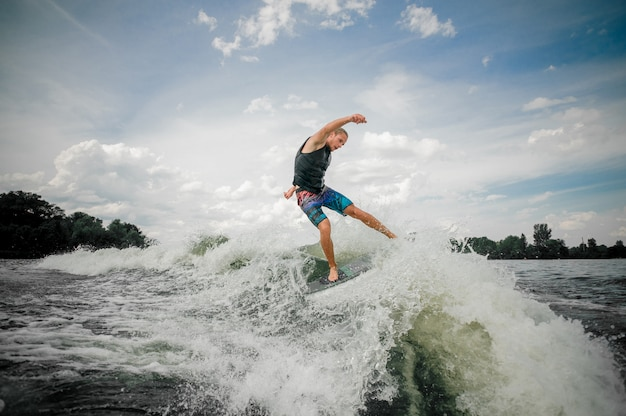 Athletic guy wakesurfing on the board down the river against the sky Premium Photo