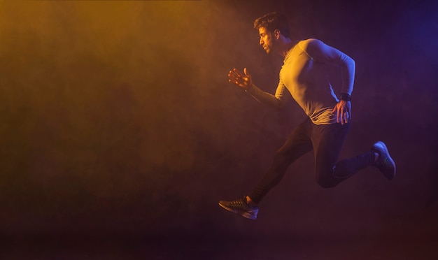 Athletic male jumping in dark studio Premium Photo
