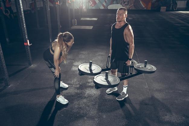 Атлетик мужчина и женщина с гантелями Бесплатные Фотографии