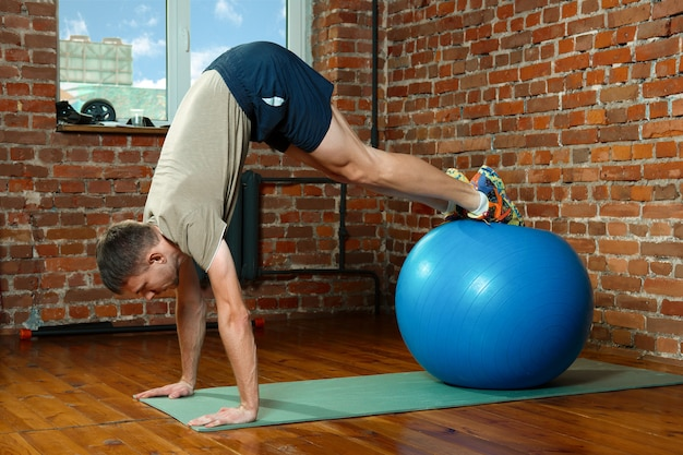Athletic man doing balancing exercises with the gym ball Premium Photo