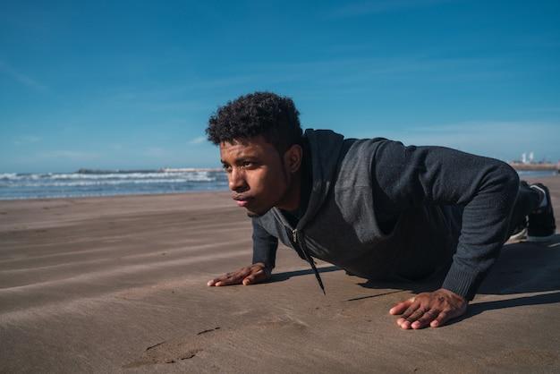 Спортивный человек делает отжимания на пляже Premium Фотографии