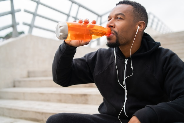 Athletic man drinking something after training. Free Photo