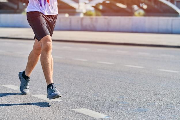 Спортивный человек, бегающий в спортивной одежде на городской дороге Premium Фотографии