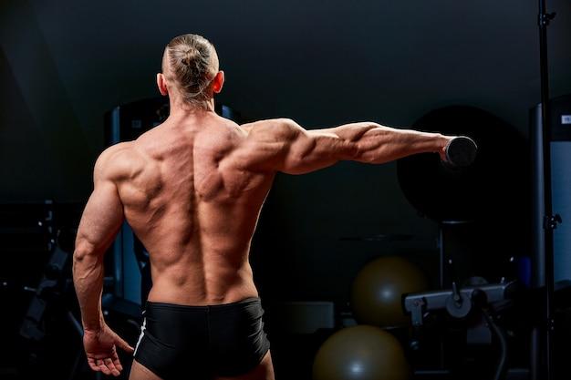 운동 남자 포즈. 검은 벽에 완벽 한 체격을 가진 남자의 사진. 다시보기. 힘과 동기 프리미엄 사진