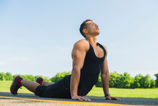 Athletic man practicing yoga outdoor Free Photo