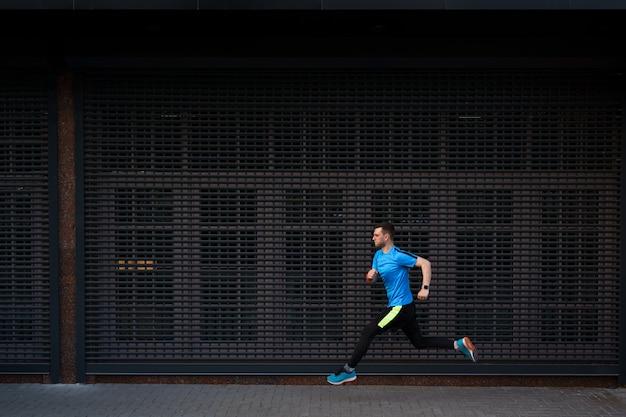 Спортивный человек бежит по городской улице на сером фоне Бесплатные Фотографии