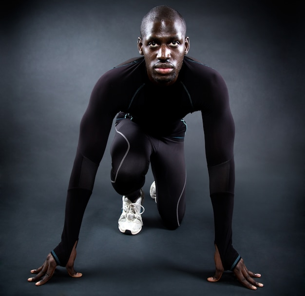 Athletic man running in black background. Free Photo