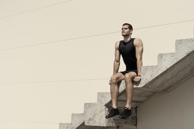 Спортивный человек, сидящий на бетонной лестнице Бесплатные Фотографии