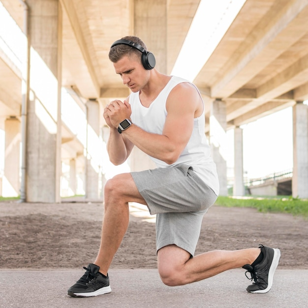 Athletic man stretching outdoors Free Photo
