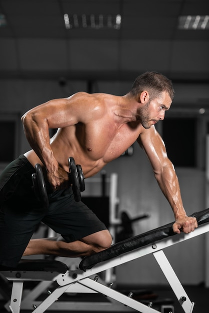 Athletic man trains with dumbbells, pumping his biceps Premium Photo