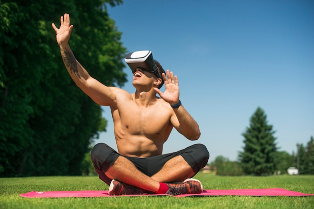 Athletic man using a virtual reality glasses outdoor Free Photo
