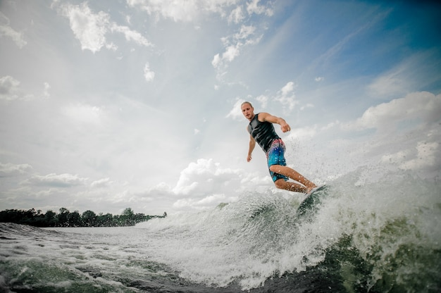 Athletic man wakesurfing on the board down the river against the sky Premium Photo