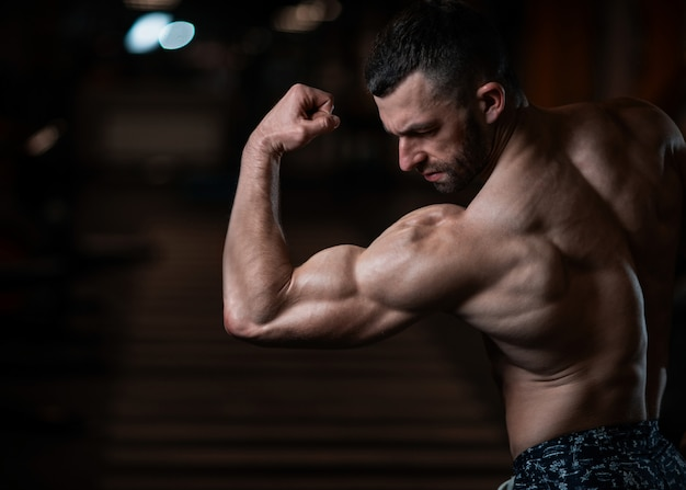 Athletic man with a muscular body poses in the gym, showing off his biceps Premium Photo