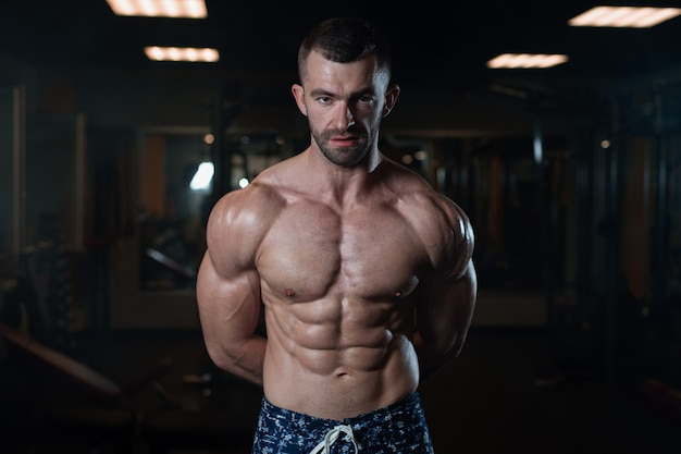 Athletic man with a muscular body poses in the gym, showing off his musclese Premium Photo