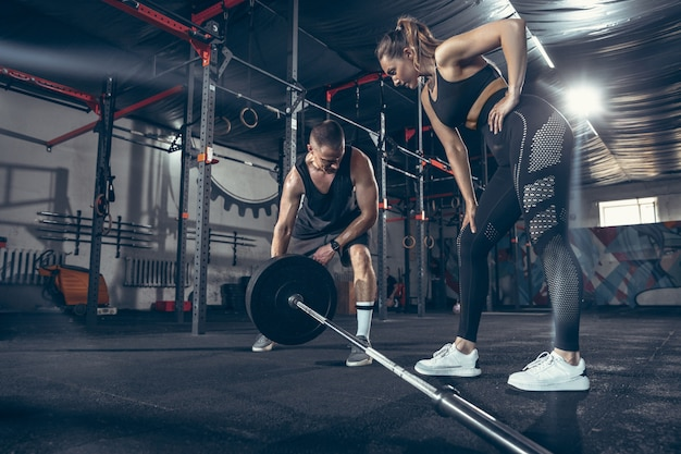 Athletic man and woman with dumbbells Free Photo