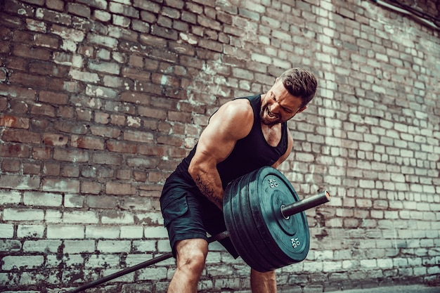 Athletic man working out with a barbell. strength and motivation. exercise for the muscles of the back Premium Photo