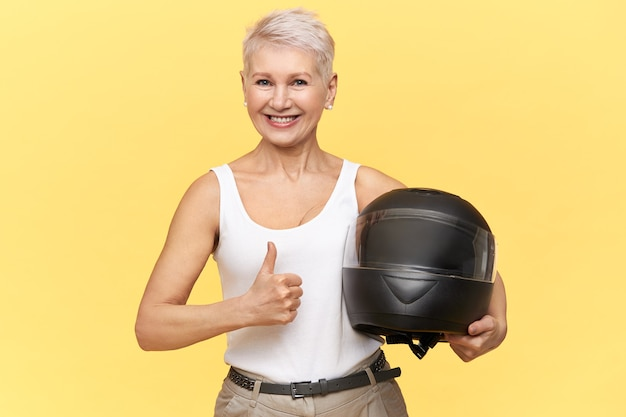 Athletic middle aged woman with blonde hair holding protective motorcycle helmet Free Photo
